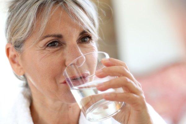 Пожилая женщина запивает таблетку