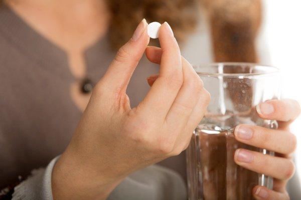 Девушка держит таблетку в руке