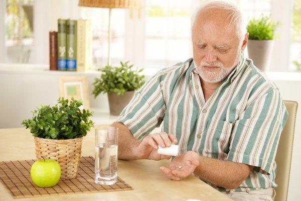 Пожилой принимает лекарство