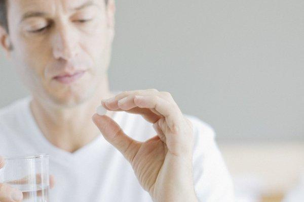 Мужчина пьет лекарства