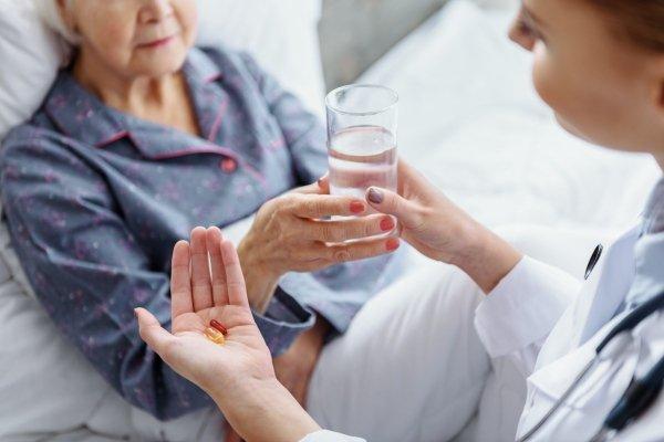 Медик дает бабушке лекарство и воду