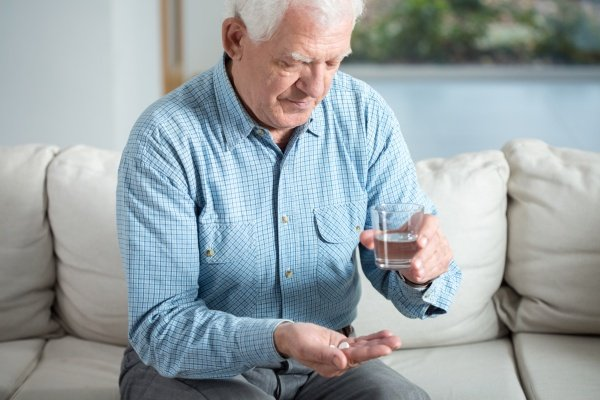 Дедушка пьет таблетку