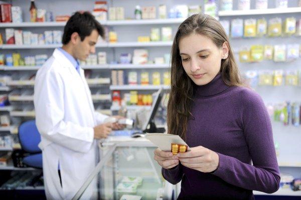 Девушка в аптеке держит таблетки